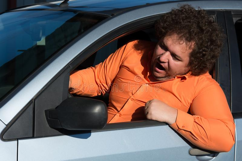 Funny fat man in the car. Funny man in the car. Road problems and difficulties in the way royalty free stock image