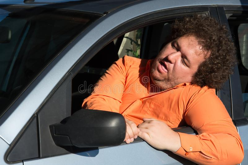 Funny fat man in the car. Funny man in the car. Road problems and difficulties in the way stock images