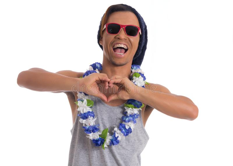 Funny man is enjoying the party. Young black man wears sunglasses, flower necklace and cap.. royalty free stock image