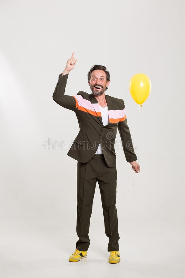 Happy man with yellow balloon. Funny man in cute black suit. Standing in funny position with yellow balloon royalty free stock photography