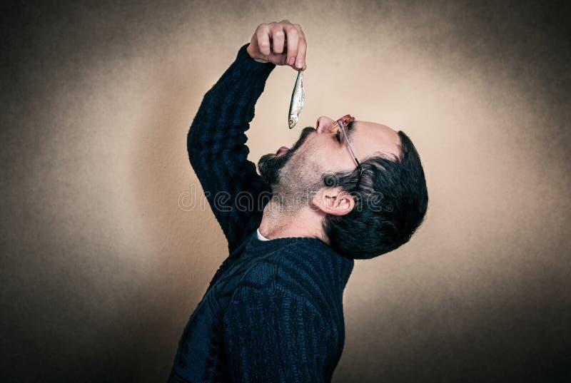 Funny man eating fish stock photos