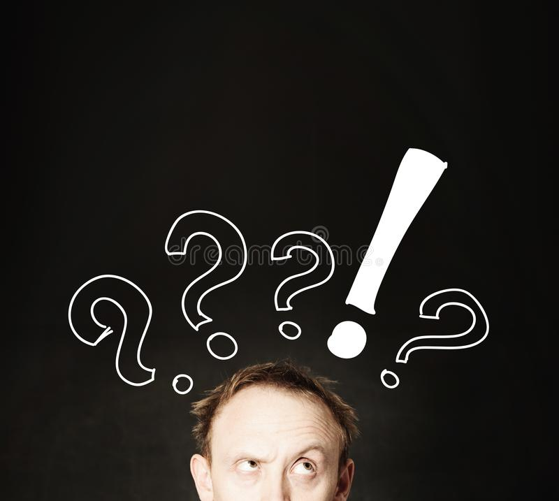 Funny man face with hand drawing question marks on blackboard background.  royalty free stock photos