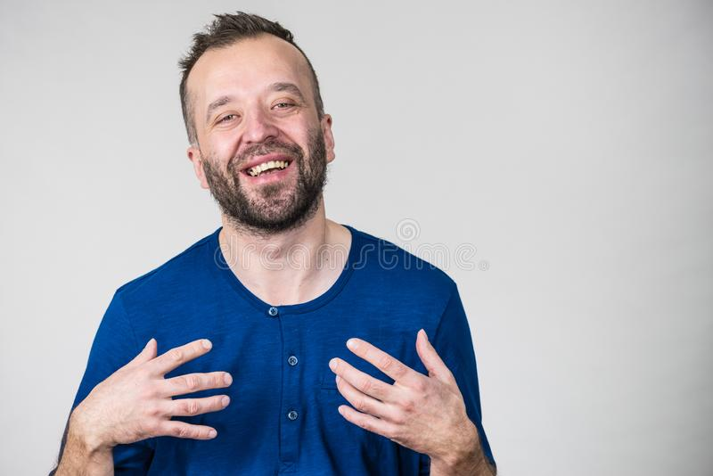 Funny man fooling around. Funny adult man, guy folling around gesturing with hands. Positive emotions concept stock photo