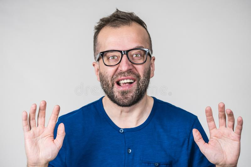 Funny man fooling around. Funny adult man wearing eyeglasses, guy folling around gesturing with hands, trying to be scary. Positive emotions concept stock images