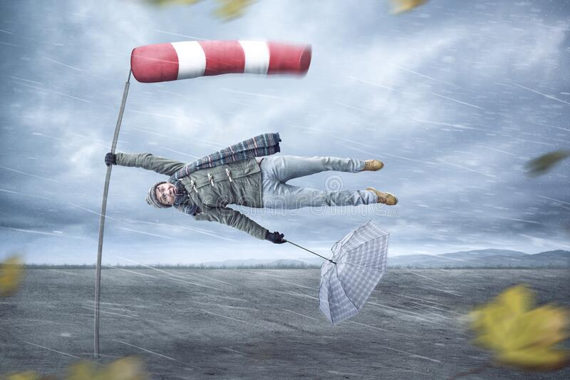 Funny man gets blown away by a storm. Funny compositing of a man holding on to a pole while being blown away by a storm. A windsock is attached to the pole stock photo
