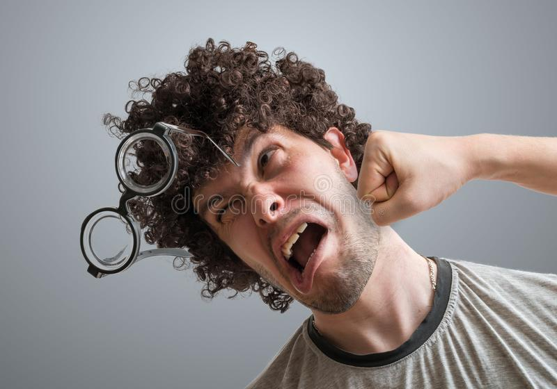 Funny man is getting punch in face with fist.  royalty free stock photos