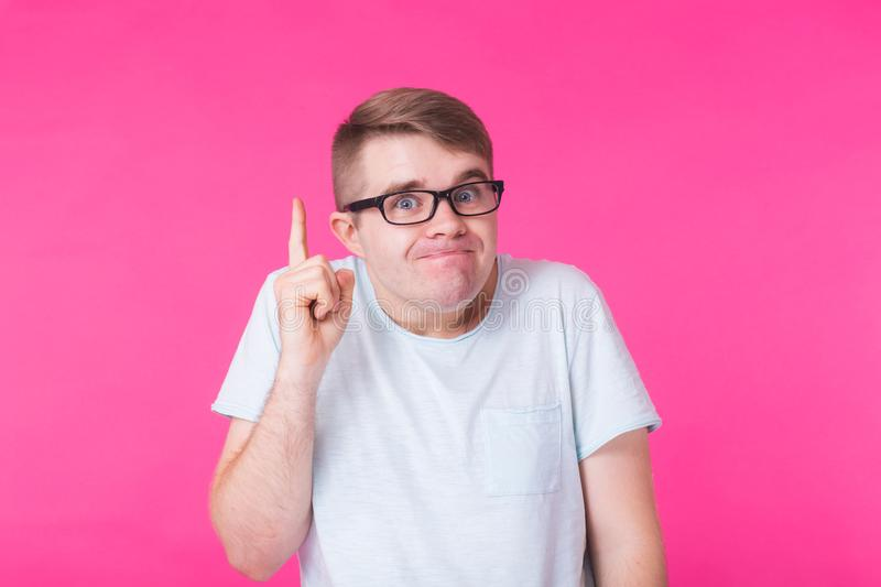Funny man with glasses has an idea, pointing with finger up on pink background. royalty free stock image