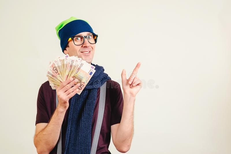 Funny man in glasses wearing header holding money and pointing on empty copy space. Male nerd with banknotes on white. Man present royalty free stock photos