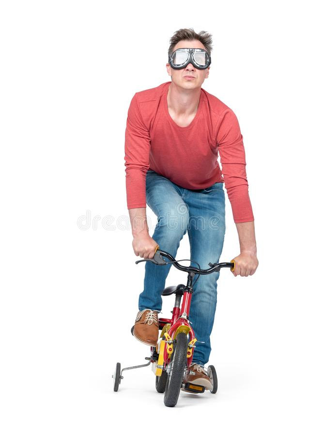 Funny man in goggles, jeans and a red t-shirt pedals a children`s bicycle, isolated on white background. royalty free stock photos