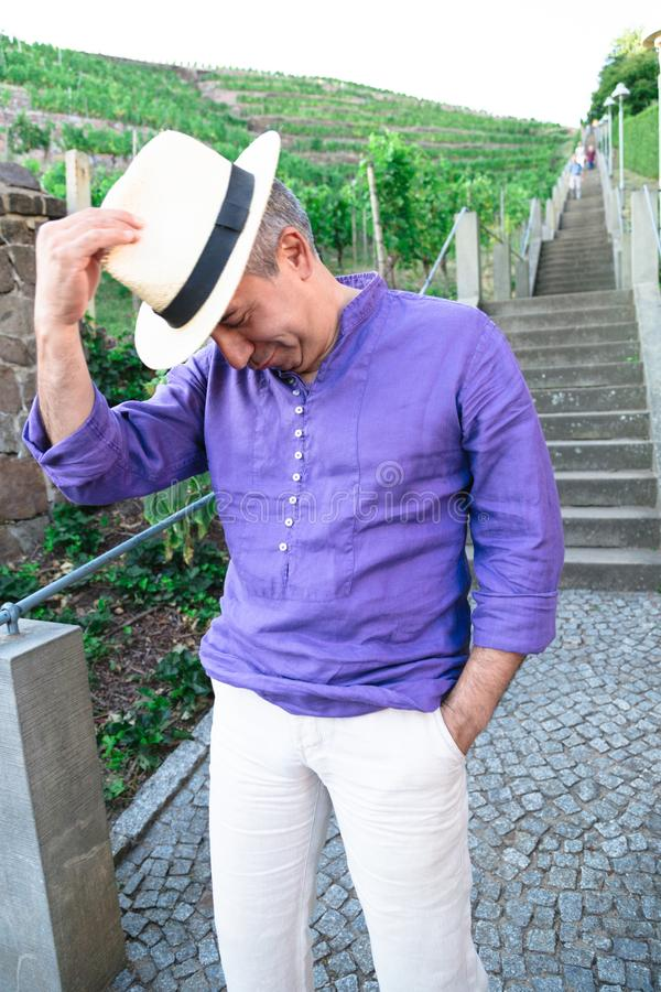 Funny man in hat is fooling around near stone stairs outdoors royalty free stock photo
