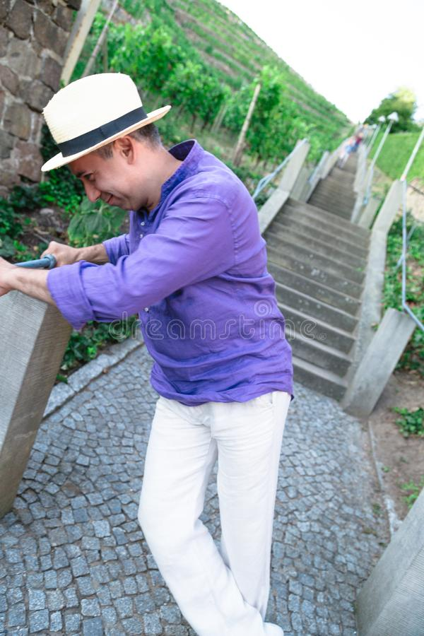 Funny man is fooling around and playing near stone staircase outdoors stock image