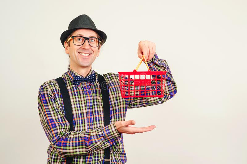 Funny man in hat and plaid shirt holding red supermarket basket. Man in shopping, isolated on white. Copy space. Seasonal or stock images