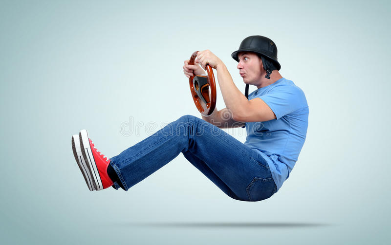 Funny man in helmet car driver with wooden steering wheel.  royalty free stock image