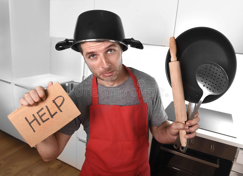 Funny man holding pan with pot on head in apron at kitchen asking for help. Funny 30s Caucasian man holding pan and household with pot on his head in red apron royalty free stock images