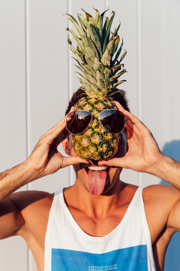 Funny man holding a pineapple in front of his face and showing a tongue stock photo