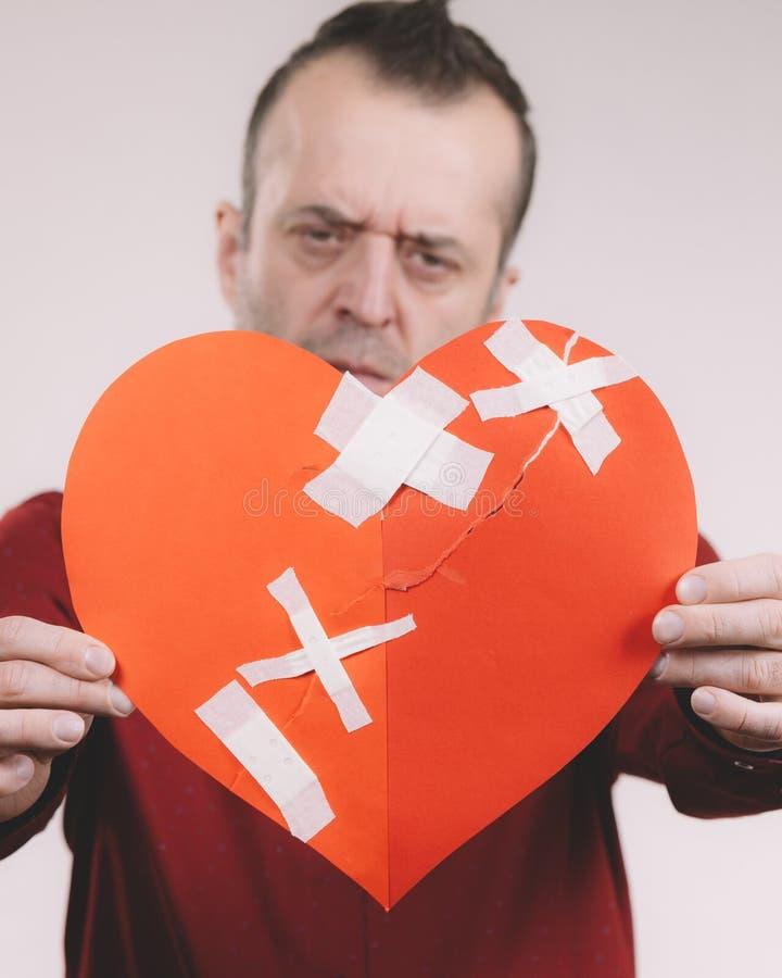 Funny man holds broken heart. Bad relationships, breaking up, emotions concept. Funny adult man holding broken heart, on grey stock images