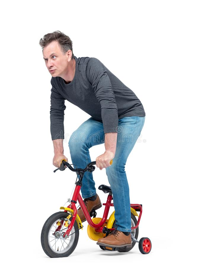 Funny man in jeans and black t-shirt pedals a children`s bicycle, isolated on white background. stock image