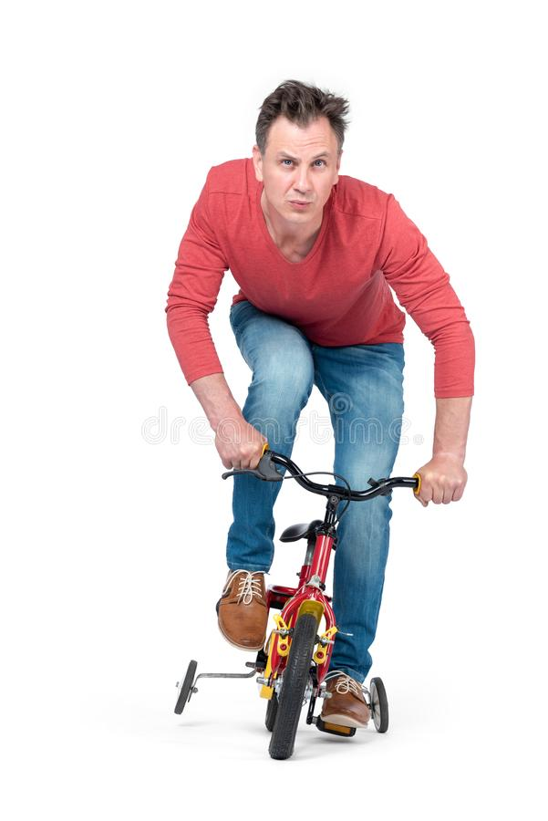Funny man in jeans and a red T-shirt is rolling on a children`s bike. Front view. Isolated on white background. royalty free stock photo