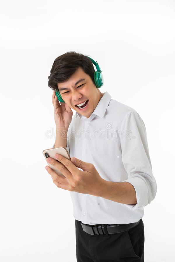 Funny man listening music with green headphone and smartphone stock images