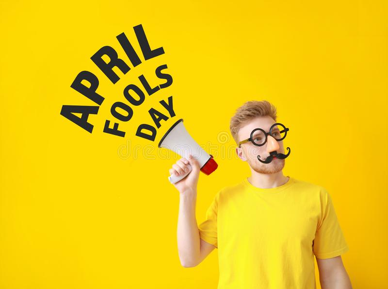 Funny man with megaphone on color background. April Fools' Day prank royalty free stock image