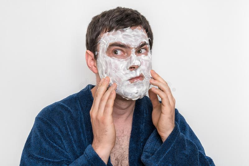 Funny man with natural white cream mask on his face royalty free stock photography