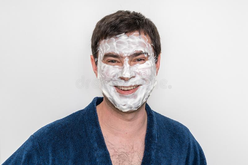 Funny man with natural white cream mask on his face stock photos