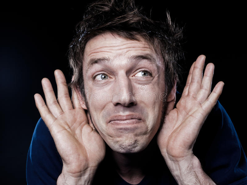 Funny Man Portrait with hearing problem. Studio portrait on black background of a funny expressive caucasian man with hearing problem royalty free stock photo