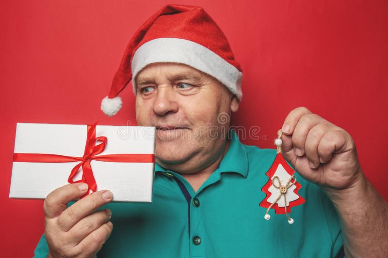 Funny man in red Christmas hat holds in hands gift box and New Year tree toy, presents for relative people and family on holidays stock photo