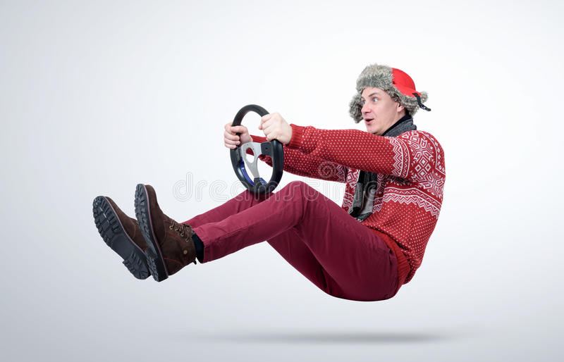 Funny man in red sweater, scarf and hat, driving car with the steering wheel.  stock image