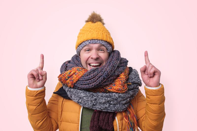 Funny man in several hats and scarfs pointing with index finger up stock images
