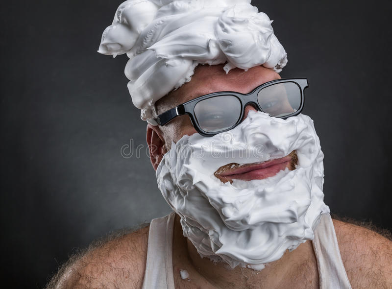 Funny man with shaving foam covered face. Strange smiling man in glasses with shaving foam on his face and on his head closeup stock image