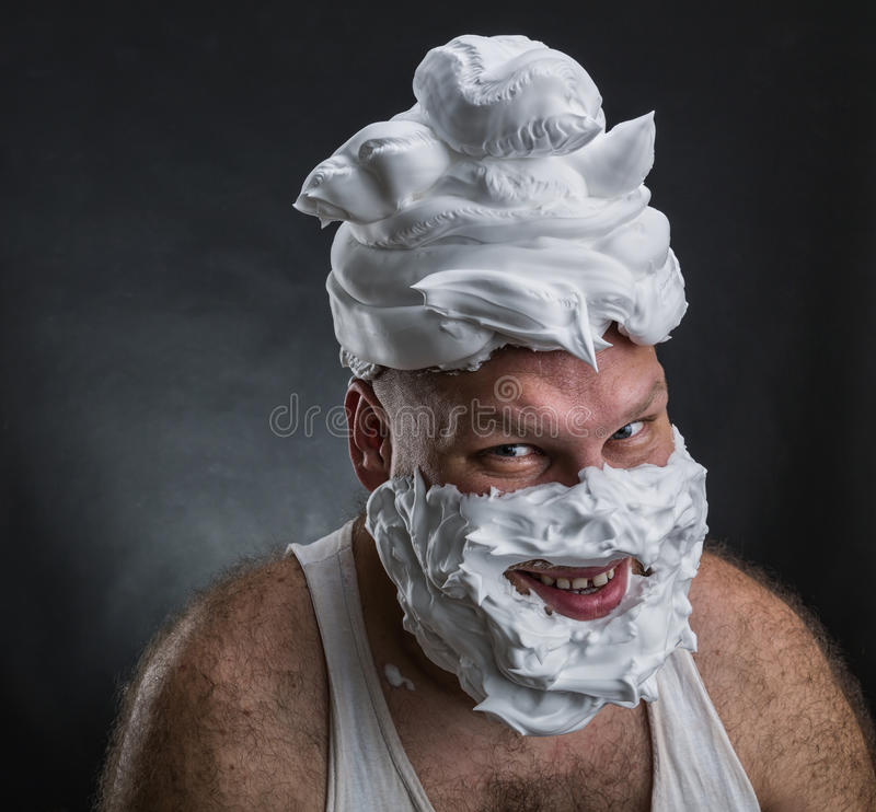 Funny man with shaving foam covered face. Strange smiling man with shaving foam on his face and on his head over grey background stock photo
