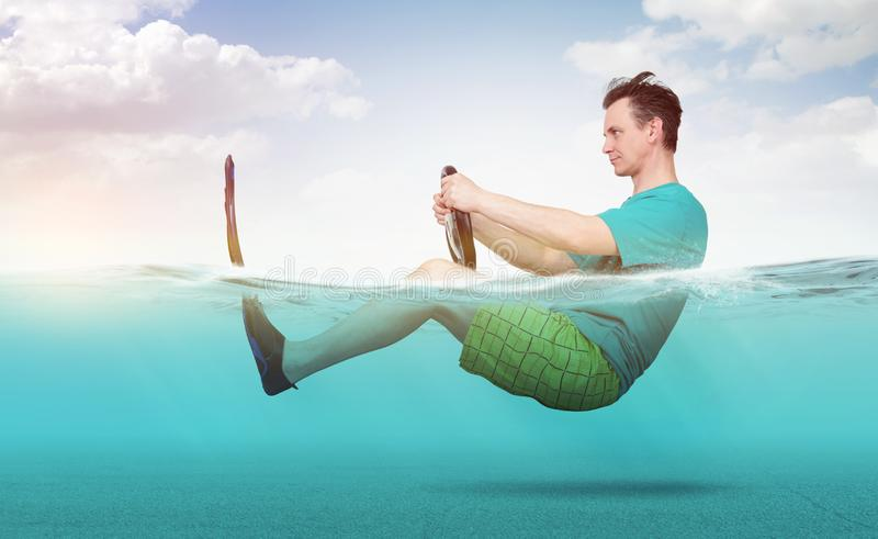 Funny man in shorts, T-shirt and flippers rides on the sea with a car steering wheel. Concept of going on vacation.  stock photo