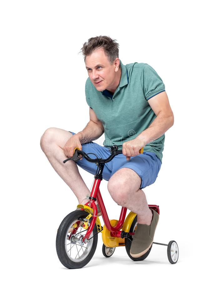 Funny man in shorts and a t-shirt rides a children`s bicycle, isolated on white background. stock image