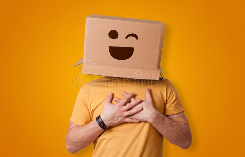 Funny man smiling with cardboard box head. Funny man wearing cardboard box on his head with smiley facen royalty free stock image