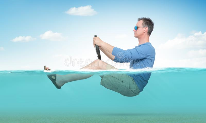 Funny man in sunglasses, shorts, T-shirt and sandals rides on the sea with a car steering wheel. Concept of going on vacation royalty free stock images
