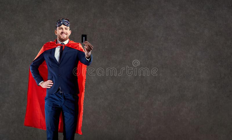 A funny man in a superhero costume keeps a credit card. A funny man in a superhero costume keeps a credit card in place for text stock image