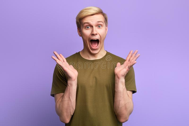 Funny man with surprsied expression, being scared to hear horrified news stock photo