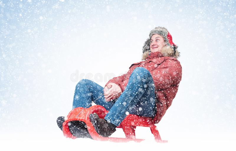 Funny man in winter clothes rides on a sled around snow. Christmas holiday concept royalty free stock photos
