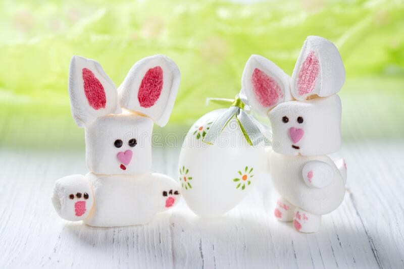 Funny marshmallow rabbits with Easter egg, sweet bunnies on a green background. Funny cute marshmallow rabbits with Easter egg, sweet bunnies on a green stock photo