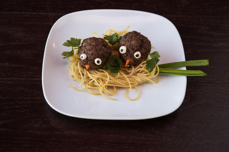 Funny meatballs with pasta. Greens and green onion for children menu royalty free stock images
