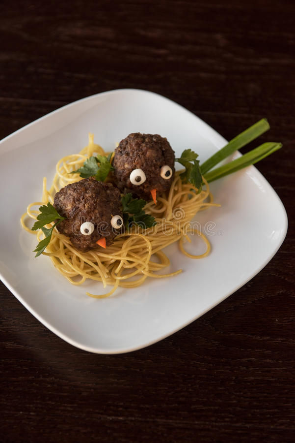 Funny meatballs with pasta. Greens and green onion for children menu royalty free stock photography