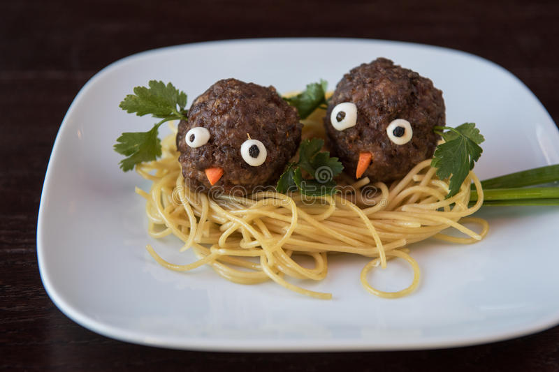 Funny meatballs with pasta. Greens and green onion for children menu royalty free stock photos