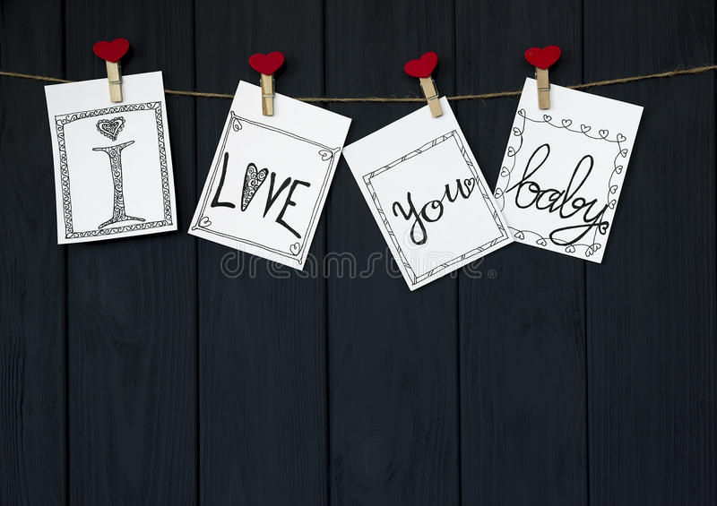 Funny Message on the four Valentine`s Cards says `I love you, baby!` natural Cord and Red pins hanging on rustic Driftwood text royalty free stock photo