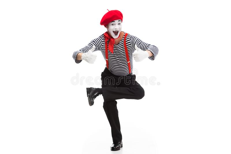 funny mime performing on one leg and showing thumbs up stock photos