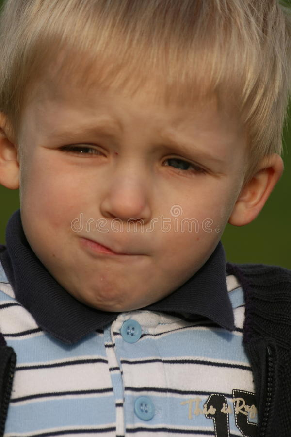 Funny mimic. Hard to say what this boy tries to express stock photo