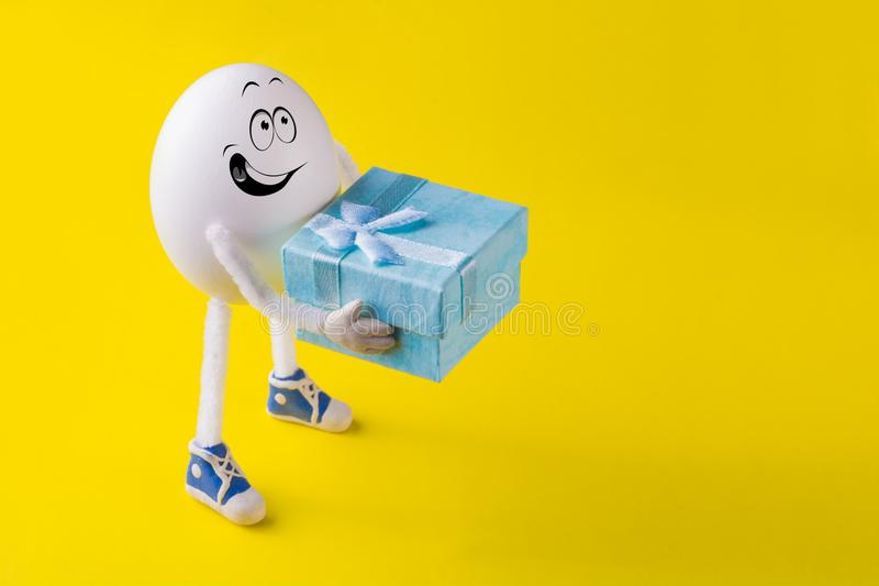 Funny miniature easter egg boy gives a present. Box against colorful background stock photos