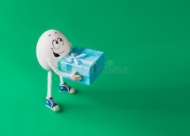 Funny miniature easter egg boy holding present box stock images