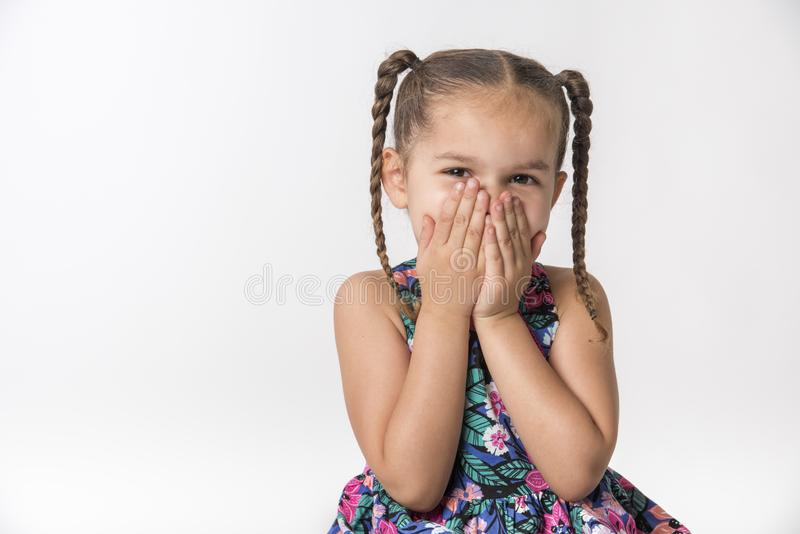 Little girls covers mouth wth hands stock photo