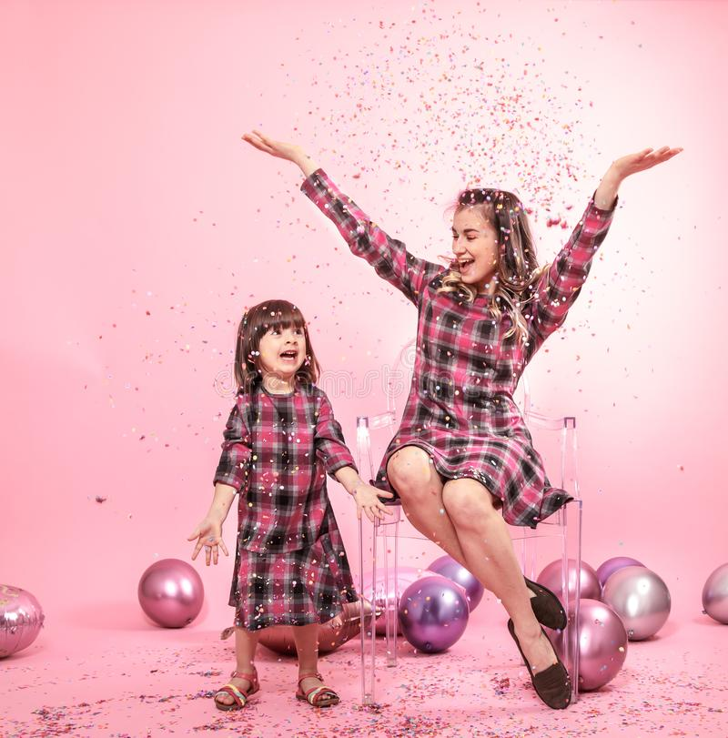 Funny mom and child sitting on a transparent stylish chairs pink background. Little girl and mother having fun with balloons and. Confetti. The concept of stock photos